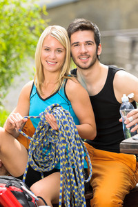 Portrait backpack active young couple sitting by terrace climbing gear