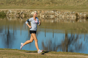 Running woman outdoor sport by river bank sunny day