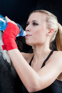 Boxing training woman pour water hold punching bag