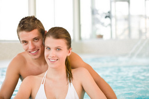 Swimming pool - young cheerful couple have fun by poolside