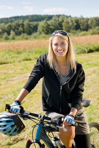Mountain biking happy sportive girl relax in meadows sunny countryside