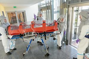 Hazardous material team pushing patient on stretcher towards hospital elevator