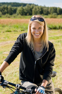 Mountain biking happy sportive girl relax in meadows sunny countryside