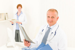 Medical doctor team senior man with female nurse hold x-ray