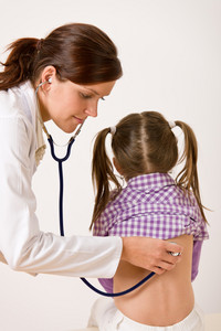 Female doctor examining child with stethoscope at medical office