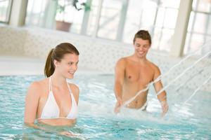 Swimming pool - young couple have fun under water stream,focus on woman in bikini