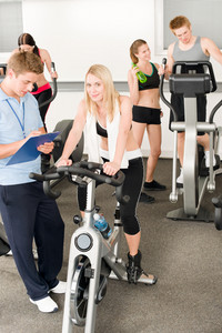 Fitness young girls at gym bicycle with instructor doing spinning