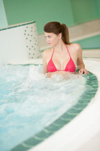 Swimming pool - beautiful woman wearing bikini, relax in bubble bath