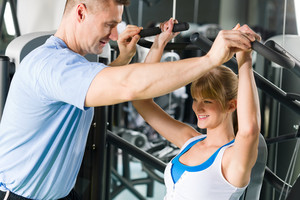 Young woman exercise on shoulder press machine with personal trainer
