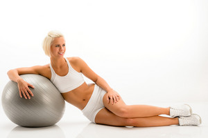 Sportive woman leaning on gym ball on white background