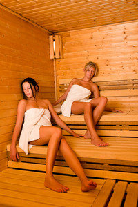 Sauna two healthy beautiful women relaxing sitting wrapped in towel