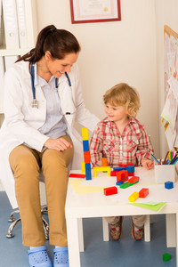 Female pediatrician playing with little girl at medical office