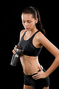 Sporty young woman with headphones and bottle on black background