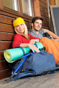 Tramping young couple backpack relax sitting by wooden cottage