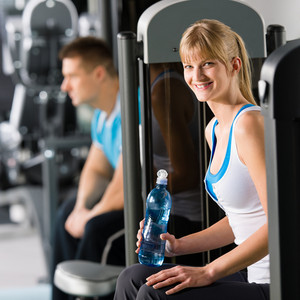 At the fitness center young woman relax on exercise machine