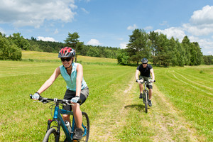 Sport couple riding mountain bicycles in coutryside meadows