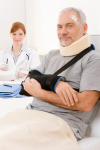 Portrait of senior patient with broken arm in doctor office