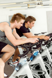 Fitness young man on gym bike spinning indoor cardio exercise