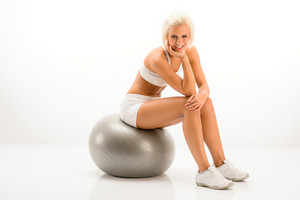 Smily blonde sitting on silver Pilates ball on white background