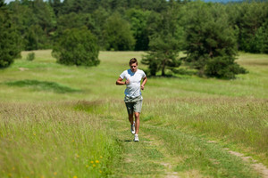 Young man with headphones jogging in a meadow,shallow DOF