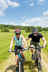 Sport mountain biking - man pushing young girl uphill sunny countryside