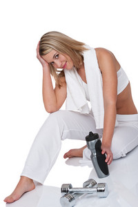 Attractive blond woman with weights and bottle of water on white background