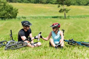 Sport mountain biking couple relax in meadows sitting drink water