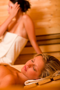 Sauna two healthy beautiful women relaxing sweating lying covered towels