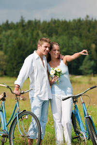 Romantic young couple walking with old bike in meadow on sunny day