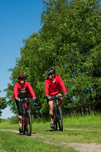 Young couple with mountine bike in spring nature on sunny day biking