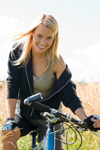 Mountain biking happy young woman relax in cornfield sunny countryside