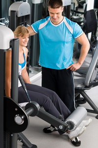 Young woman with personal trainer look at exercise chart at gym