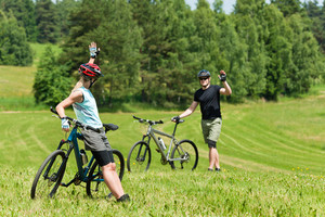 Sport mountain biking happy couple greeting in meadows sunny countryside