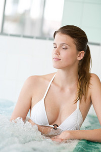 Swimming pool - beautiful woman wearing bikini, relax in bubble bath