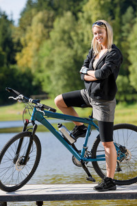 Mountain biking young woman standing on pier looking natural lake