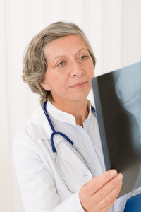 Senior doctor female hold and looking at x-ray with stethoscope