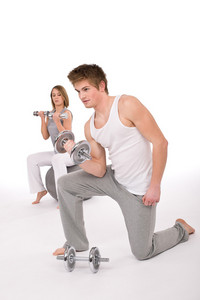 Fitness - Young healthy couple exercise with metal weights on white background