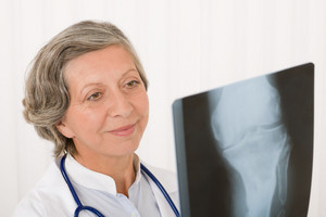 Happy senior doctor female looking at x-ray with stethoscope portrait