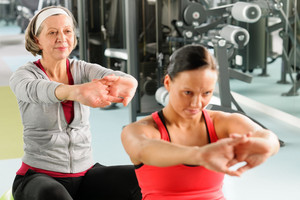 Senior woman with personal fitness trainer stretch out at gym