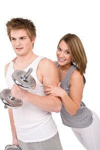 Fitness - Smiling healthy couple exercising with weights on white background