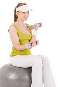 Fitness teenager woman with dumbbell sit on ball in sportive outfit