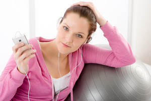 Fitness portrait of woman listen music mp3 relax in gym