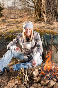Campfire hiking woman with backpack cook in countryside