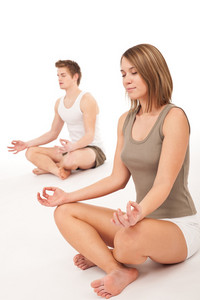 Fitness - Healthy couple stretching in yoga position on white background