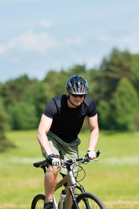 Fit young man cycling uphill mountain bike in summer coutryside