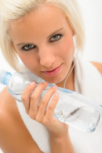 Fitness blond woman hold water bottle with headphones isolated white