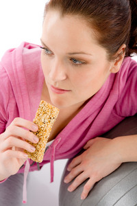 Fitness woman eat granola bar sportive outfit in gym