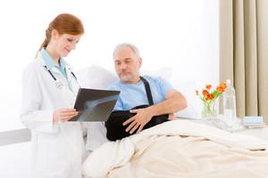 Hospital - female doctor examine x-ray of senior patient