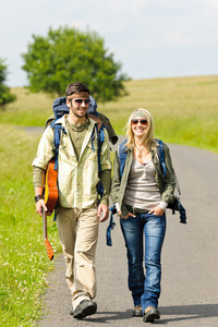 Hiking young couple backpack tramping on asphalt road sunny countryside