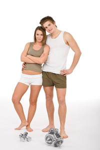 Fitness - Young healthy couple with weights in sportive outfit on white background